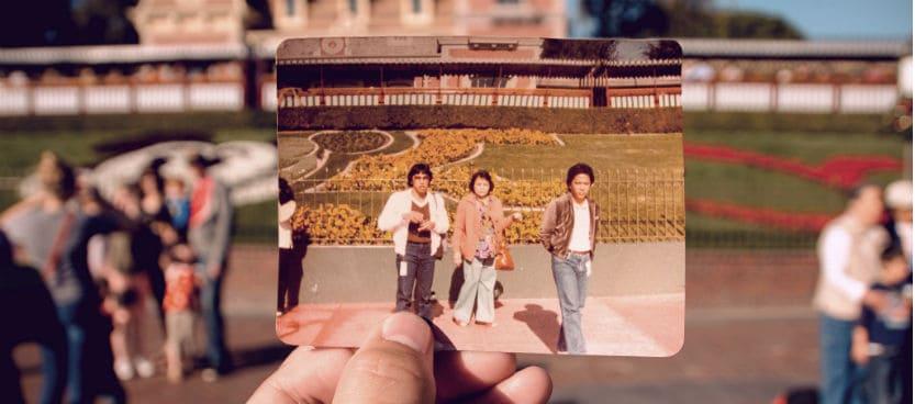 old photo held in front of scene at disneyworld